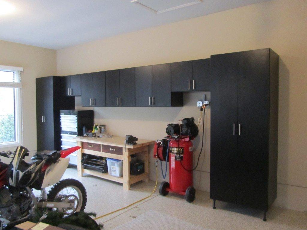 Black Garage Cabinets Surround The Homeowneru0027s Tool Box And Compressor.