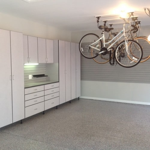 Gray cabinets, slatwall, and overhead bike hoists solve storage issues